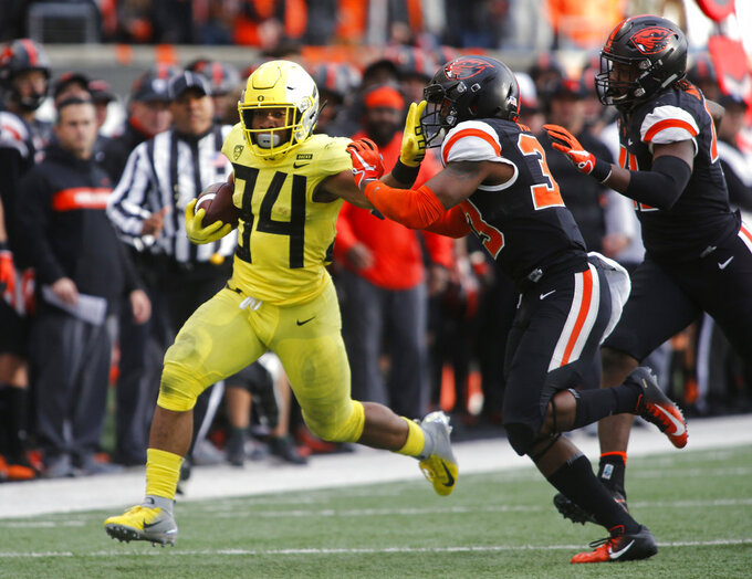 Oregon running back C.J. Verdell (34) tries to stiff-arm Oregon State safety Jalen Moore (33) on a run during the second half of an NCAA college football game in Corvallis, Ore., Friday, Nov. 23, 2018. Oregon won 55-15. (AP Photo/Timothy J. Gonzalez)