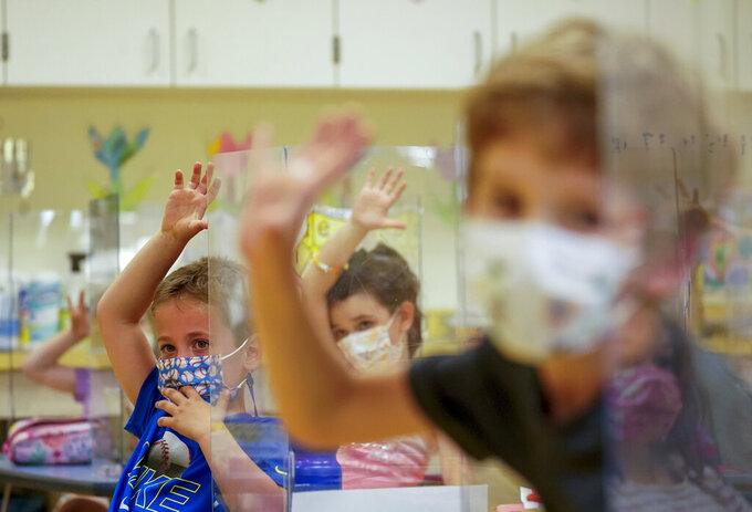 FILE - This Tuesday May 18, 2021 file photo shows kindergarten students wearing face masks and separated by plexiglass during a math lesson at the Milton Elementary School in Rye, N.Y. New York plans to make mask-wearing optional in K-12 schools starting Monday, June 7, 2021 the state's health commissioner said in a letter to federal health regulators Friday. (AP Photo/Mary Altaffer, File)