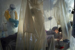 In this Saturday, July 13, 2019 photo, health workers wearing protective gear check on a patient isolated in a plastic cube at an Ebola treatment center in Beni, Congo. On July 17, the World Health Organization declared the Ebola outbreak an international emergency after it spread to eastern Congo's biggest city, Goma. (AP Photo/Jerome Delay)