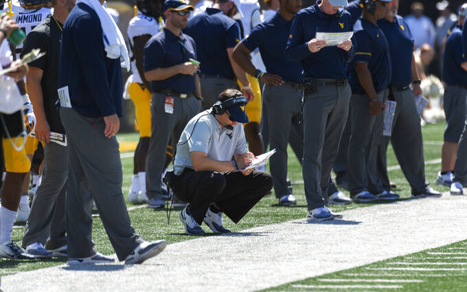 West Virginia head coach Neal Brown looks over his play book as he squats on the sideline during the second half of an NCAA college football game against Missouri Saturday, Sept. 7, 2019, in Columbia, Mo. Missouri won the game 38-7. (AP Photo/L.G. Patterson)