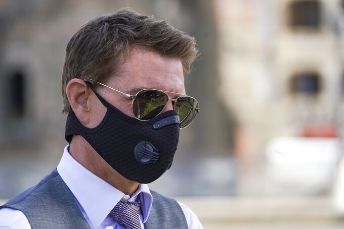 """FILE - In this Tuesday, Oct. 13, 2020 file photo, actor Tom Cruise wears a face mask to prevent the spread of COVID-19 as he greets fans during a break from shooting Mission Impossible 7, along Rome's Fori Imperiali avenue. Tom Cruise has launched an expletive-laden rant at colleagues on the set of his latest """"Mission: Impossible"""" movie after he reportedly spotted two workers failing to abide by social distancing rules. In audio released Wednesday, Dec. 16 by the Sun tabloid, the 58-year-old Hollywood megastar can be heard warning that anyone caught not following the rules to stay at least 2 meters (more than 6.5 feet) away from others will be fired. (AP Photo/Andrew Medichini, file)"""
