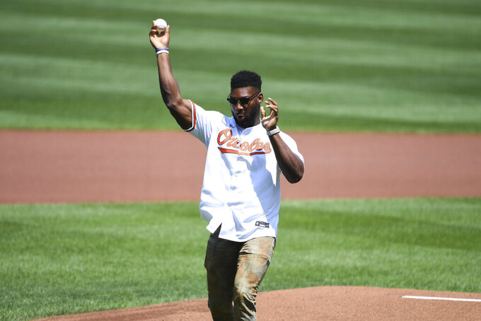 Baltimore Ravens' Tyus Bowser throws out the ceremonial first pitch before a baseball game between the Baltimore Orioles and the Tampa Bay Rays, Sunday, Aug. 8, 2021, in Baltimore. (AP Photo/Terrance Williams)
