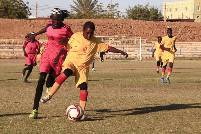 In this Wednesday, Dec. 11, 2019 photo, Sudanese al-Difaa, in yellow, and al-Sumood women teams play in Omdurman, Khartoum's twin city, Sudan. The women's soccer league has become a field of contention as Sudan grapples with the transition from three decades of authoritarian rule that espoused a strict interpretation of Islamic Shariah law. (AP Photo)