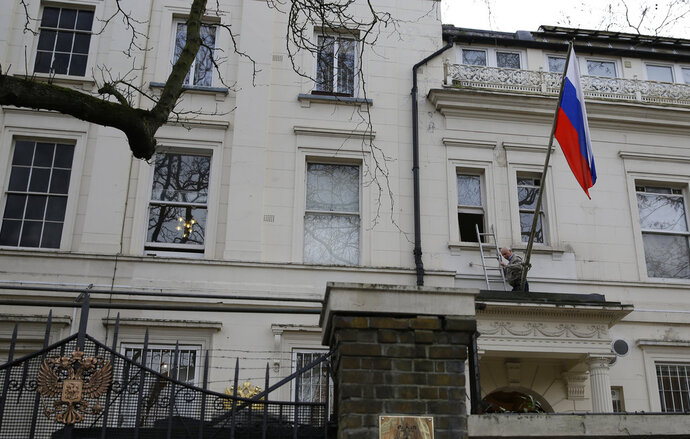 A man works to untangle the national flag flown from the Russian Embassy, after it became entangled on its staff at the embassy in London, Wednesday, March 14, 2018. Britain announced Wednesday it will expel 23 Russian diplomats, the biggest such expulsion since the Cold War, and break off high-level contacts with the Kremlin over the nerve-agent attack on a former spy and his daughter in an English town.(AP Photo/Alastair Grant)