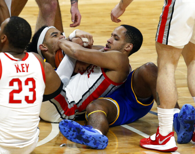Ohio State guard CJ Walker, right, and Morehead State forward Johni Broome wrestle for the ball during the first half of an NCAA college basketball game in Columbus, Ohio, Wednesday, Dec. 2, 2020. (AP Photo/Paul Vernon)