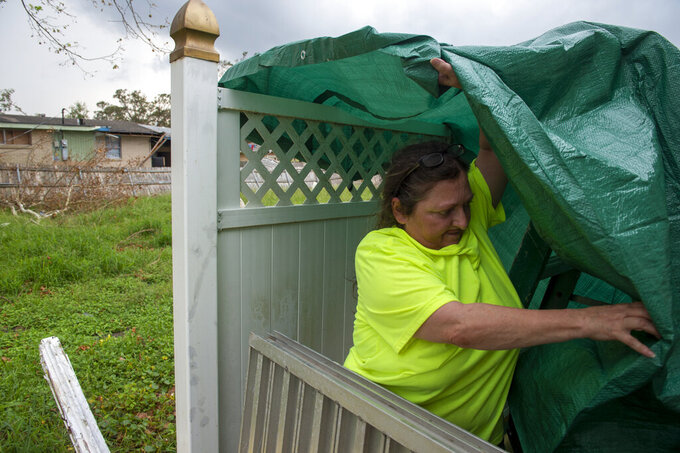 Vickey Schneider secures a tarp around the edge of her family's roof in Kenner, La., where they also keep their generator, Monday, Sept. 6, 2021, a week after Hurricane Ida swept through the area. (Chris Granger/The Times-Picayune/The New Orleans Advocate via AP)