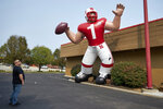 A Nebraska fan stops to look at a giant inflatable football player standing in front of the Husker Hounds sports apparel store in Omaha, Neb., Wednesday, Sept. 16, 2020. It was put up Wednesday after the Big Ten conference changed course Wednesday and said it plans to begin its NCAA college football season the weekend of Oct. 23-24. Each team will have an eight-game schedule. (AP Photo/Nati Harnik)