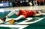 Virginia Tech guard Justin Robinson writhes in pain after a play during the second half of the team's NCAA college basketball game against Miami, Wednesday, Jan. 30, 2019, in Coral Gables, Fla. (AP Photo/Wilfredo Lee)