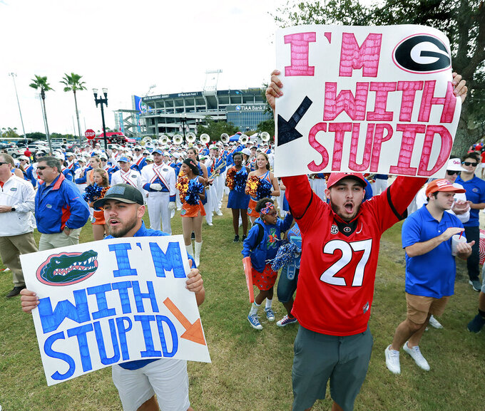 FILE - In this Oct. 27, 2018, file photo, friendly rivals Justin Passmore, left, and Dylan Streeter support their teams outside TIAA Bank Field before the NCAA college football game between Georgia and Florida in Jacksonville, Fla. Florida and Georgia agreed to keep their annual rivalry game in Jacksonville through 2023, and each school will get a significant payout bump. (Curtis Compton/Atlanta Journal-Constitution via AP, File)