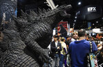 Marielle Larson, 3, looks over her father Derek's shoulder at an oversized Godzilla model on the convention floor during Preview Night at the 2019 Comic-Con International: San Diego, Wednesday, July 17, 2019, in San Diego, Calif. (Photo by Chris Pizzello/Invision/AP)