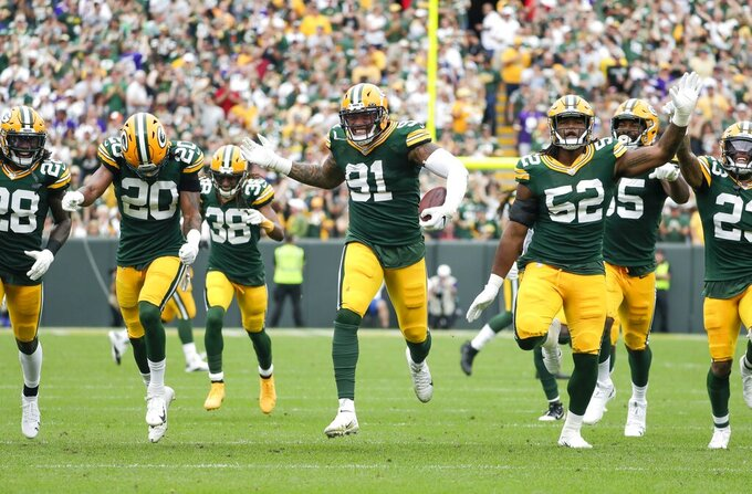 Green Bay Packers' Preston Smith celebrates his interception with teammates during the first half of an NFL football game against the Minnesota Vikings Sunday, Sept. 15, 2019, in Green Bay, Wis. (AP Photo/Morry Gash)