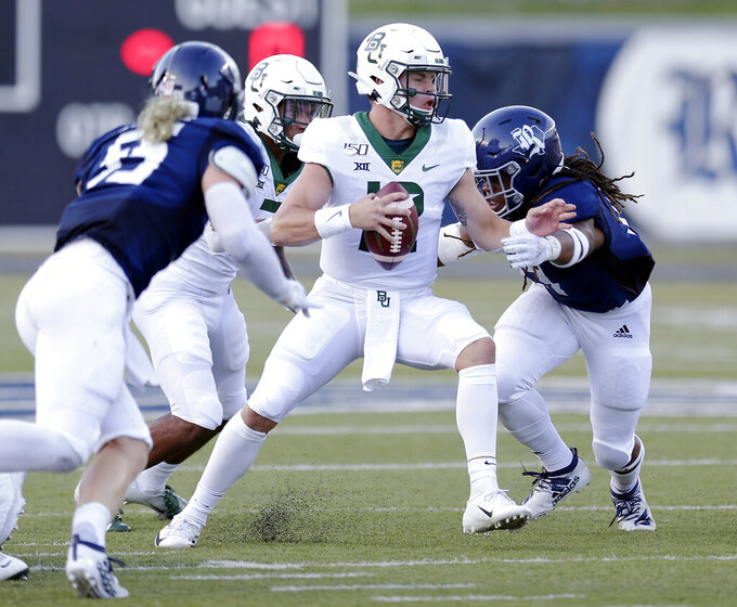 Baylor quarterback Charlie Brewer, middle, is sacked by Rice linebacker Blaze Alldredge (55) and linebacker Treshawn Chamberlain, right, during the first half of an NCAA college football game Saturday, Sept. 21, 2019, in Houston. (AP Photo/Michael Wyke)