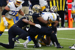 Los Angeles Chargers running back Joshua Kelley (27) is stopped by New Orleans Saints defensive tackle Shy Tuttle (99) and defensive tackle Sheldon Rankins (98) in the first half of an NFL football game in New Orleans, Monday, Oct. 12, 2020. (AP Photo/Brett Duke)