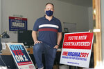 Redistricting reform advocate Brian Cannon poses with some of his yard signs and bumper stickers in his office, Tuesday Oct. 6, 2020, in Richmond, Va.  An effort to end centuries of partisan gerrymandering in Virginia is up for consideration by the state's voters.  (AP Photo/Steve Helber)