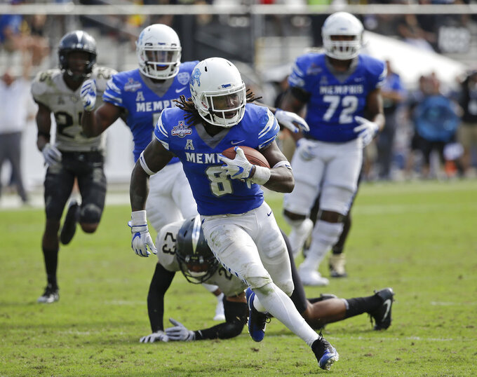 FILE - In this Dec. 2, 2017, file photo, Memphis running back Darrell Henderson, front, runs past Central Florida defensive back Tre Neal (23) for a 30-yard touchdown during the first half of the American Athletic Conference championship NCAA college football game in Orlando, Fla. Memphis carries a four-game winning streak into Saturday's American Athletic Conference championship game against No. 7 Central Florida. (AP Photo/John Raoux, File)