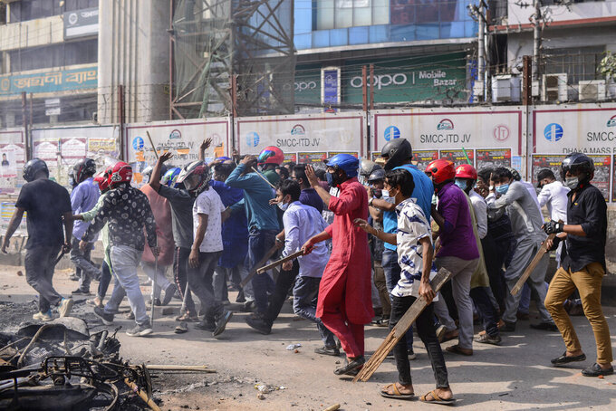 A group of protestors walk with wooden sticks  during a clash with another group  after Friday prayers at Baitul Mokarram mosque in Dhaka, Bangladesh, Friday, March 26, 2021. Witnesses said violent clashes broke out after one faction of protesters began waving their shoes as a sign of disrespect to Indian Prime Minister Narendra Modi, and another group tried to stop them. Local media said the protesters who tried to stop the shoe-waving are aligned with the ruling Awami League party. The party criticized the other protest faction for attempting to create chaos in the country during Modi's visit. (AP Photo/Mahmud Hossain Opu)