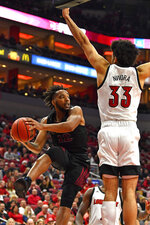 North Carolina Central guard Jordan Perkins (12) looks to pass around the defense of Louisville forward Jordan Nwora (33) during the first half of an NCAA college basketball game in Louisville, Ky., Sunday, Nov. 17, 2019. (AP Photo/Timothy D. Easley)