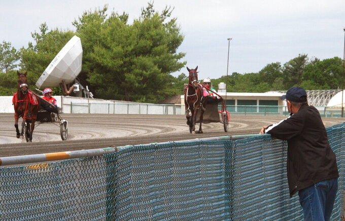 A man watches horses warm up before the first race at Freehold Raceway in Freehold N.J. on Friday, May 28, 2021, the day that New Jersey's indoor mask mandate ended. About 20% of early arrivers at the track were wearing masks. (AP Photo/Wayne Parry)