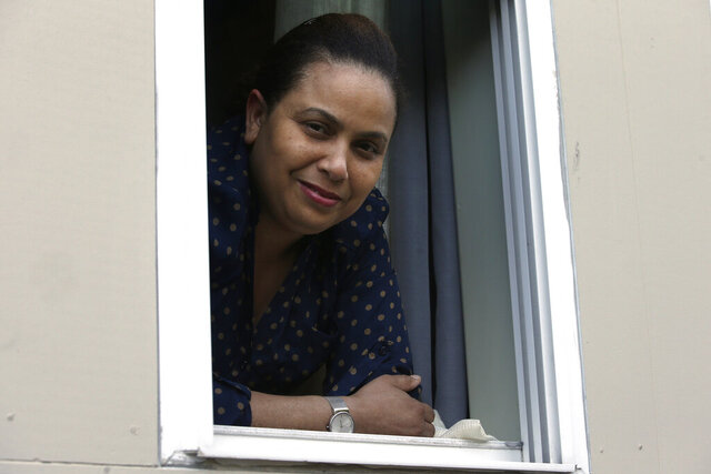 In this Wednesday, May 20, 2020, photo, Wendy De Los Santos, originally from Dominican Republic, stands for a photograph in a window of her home, in Malden, Mass. The 38-year-old Massachusetts resident passed her test to become a U.S. citizen in mid-March, the day before businesses and government offices across her state were ordered shutdown over the spread of the coronavirus. (AP Photo/Steven Senne)
