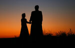 FILE - In this Oct. 25, 2017, file photo, a woman and a young girl hold hands for a photograph, in Colorado City, Ariz. They are members of a community on the Utah-Arizona border that has been home for more than a century to a polygamous sect that is an offshoot of mainstream Mormonism. The recent slaying in Mexico of nine people who belonged to a Mormon offshoot community where some people practice polygamy shines a new spotlight on the ongoing struggle for the mainstream church to fight the association with plural marriage groups because of its past. (AP Photo/Rick Bowmer, File)