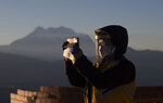 A city employee wearing a face mask amid the spread of the new coronavirus takes a selfie with the first rays of sunlight during a new year's ritual at the Mirador Jach'a Apacheta de Munaypata, in La Paz, Bolivia, early Sunday, June 21, 2020. Aymara indigenous communities are celebrating the Andean new year 5,528. (AP Photo/Juan Karita)