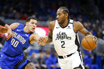 Los Angeles Clippers forward Kawhi Leonard (2) drives past Orlando Magic forward Aaron Gordon (00) during the first quarter of an NBA basketball game in Orlando, Fla., Sunday, Jan. 26, 2020. (AP Photo/Reinhold Matay)