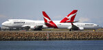 FILE - In this Aug. 20, 2015, file photo, two Qantas planes taxi on the runway at Sydney Airport in Sydney, Australia. The outbreak of the new virus threatens to erase $29 billion of this year's revenue for global airlines, mostly for Chinese carriers, as travel crashes worldwide, according to the International Air Transport Association. International airlines including British Airways, Germany's Lufthansa, Australia's Qantas and the three largest U.S. airlines have suspended flights to China, in some cases until late April or May. (AP Photo/Rick Rycroft, File)