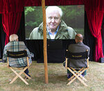 In this undated handout photo issued by WWF on Saturday, Sept. 26, 2020, British Naturalist Sir David Attenborough, sits with Prince William for a private outdoor screening of his upcoming film, David Attenborough: A Life On Our Planet, at Kensington Palace, London.(WWF via AP)