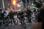 Police cycle in to arrest protesters refusing to get off the streets during an imposed curfew while marching in a solidarity rally calling for justice over the death of George Floyd, Tuesday, June 2, 2020, in New York. Floyd died after being restrained by Minneapolis police officers on May 25. (AP Photo/Wong Maye-E)
