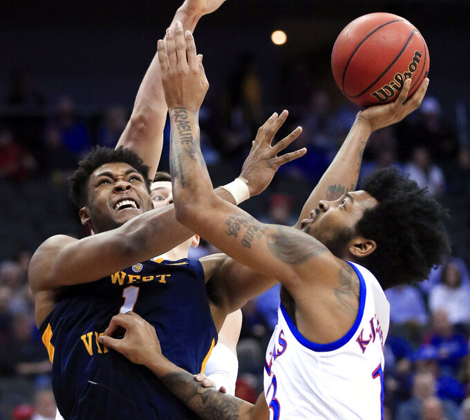 West Virginia forward Derek Culver (1) shoots while defended by Kansas guard K.J. Lawson (13) during the second half of an NCAA college basketball game in the semifinals of the Big 12 men's tournament in Kansas City, Mo., Friday, March 15, 2019. Kansas defeated West Virginia 88-74. (AP Photo/Orlin Wagner)