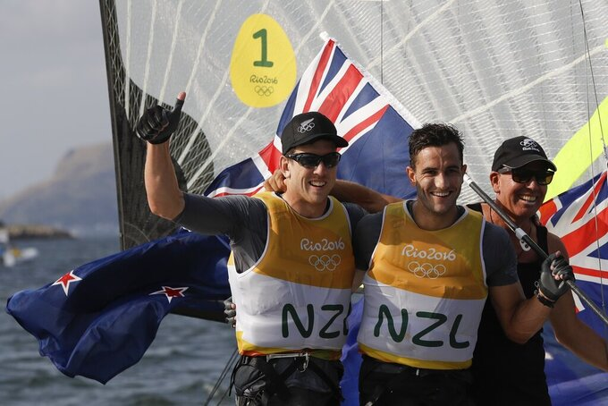 FILE - In this Aug. 18, 2016, file photo, New Zealand's Peter Burling, left, and Blair Tuke, center, celebrate their 49er FX men gold medal at the Summer Olympics in Rio de Janeiro. As they hit what could be the prime of their careers, Burling, 30, and Tuke, 31, are thinking about more than just their next victory. Sure, they're focusing in on trying to win another gold medal in the high-performance 49er skiff in the Tokyo Olympics starting later this month. They also realize that as the victories pile up, they're in a unique position to speak out about protecting the planet's oceans. (AP Photo/Bernat Armangue, File)