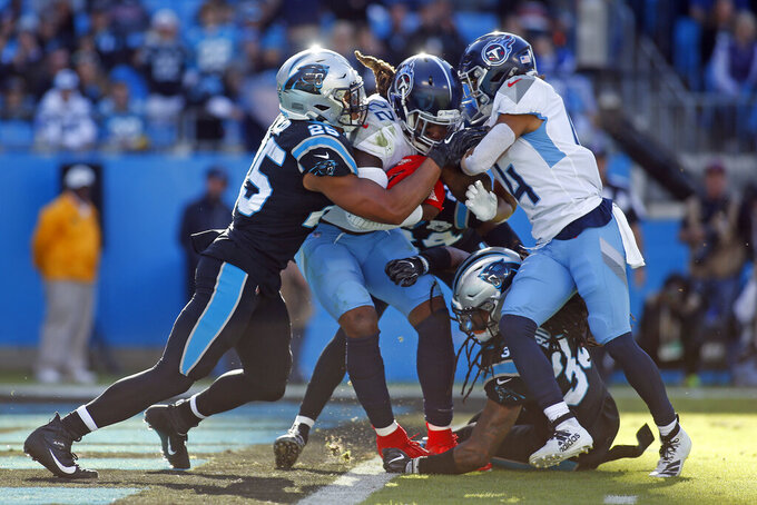 Tennessee Titans running back Derrick Henry (22) scores a touchdopwn while Carolina Panthers strong safety Eric Reid (25) tries to stop the runner while Titans wide receiver Kalif Raymond (14) pushes during the second half of an NFL football game in Charlotte, N.C., Sunday, Nov. 3, 2019. (AP Photo/Brian Blanco)