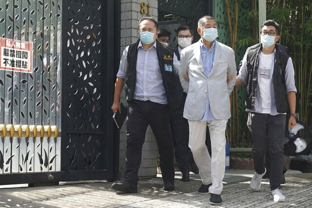 Hong Kong media tycoon Jimmy Lai, center, who founded local newspaper Apple Daily, is arrested by police officers at his home in Hong Kong, Monday, Aug. 10, 2020. Lai was arrested Monday on suspicion of collusion with foreign powers, his aide said, in the highest-profile use yet of the new national security law Beijing imposed on the city after protests last year. (AP Photo)