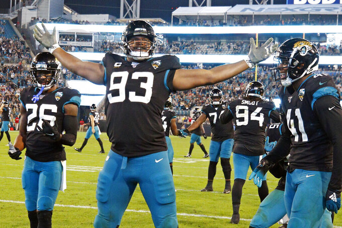Jacksonville Jaguars defensive end Calais Campbell (93) celebrates his touchdown against the Indianapolis Colts on a fumble recovery with safety Jarrod Wilson (26) and linebacker Josh Allen (41) during the second half of an NFL football game, Sunday, Dec. 29, 2019, in Jacksonville, Fla. (AP Photo/Stephen B. Morton)