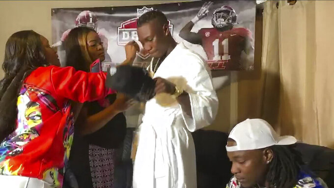 In this still image from video provided by the NFL, Henry Ruggs III, center, gets ready to put on a Las Vegas Raiders cap after being selected by the team in the first round of the NFL football draft Thursday, April 23, 2020. (NFL via AP)