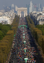 FILE - In this Sunday, April 14, 2019 file photo, the start of the men's race for the Paris Marathon looking towards the Arc de Triomphe, in Paris, France. The Paris Marathon has been canceled because of the coronavirus after repeated attempts to find a new date, organizers said Wednesday, Aug. 12, 2020. The race was originally due to take place in April but was then moved to October. Organizers said they'd recently tried to rearrange the race for November but continuing travel restrictions made that unrealistic  (AP Photo/Thibault Camus, File)
