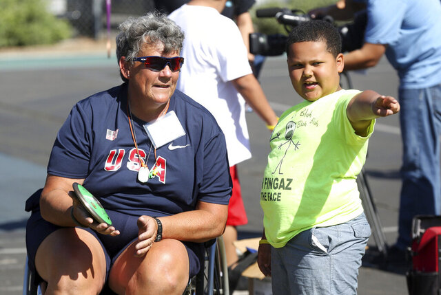 FILE - In this May 2, 2015, file photo, Paralympian Angela Madsen, left, works with Los Angeles Unified School District students during Ready, Set, Gold! Day at Trinity Street Elementary in Los Angeles. The U.S. Coast Guard says the body Madsen, who was rowing from California to Hawaii, is headed to Tahiti. A friend of Madsen, 60, a paraplegic Marine Corps veteran, contacted the Coast Guard on Sunday, June 21, 2020, after not hearing from her for more than 24 hours. The next day, a National Guard air crew flew over her last known location more than 1,000 miles off Hawaii and spotted her lifeless body in the water, tethered to her boat. A boat en route to Tahiti retrieved her body. (Photo by Matt Sayles/Invision for Samsung/AP Images, File)