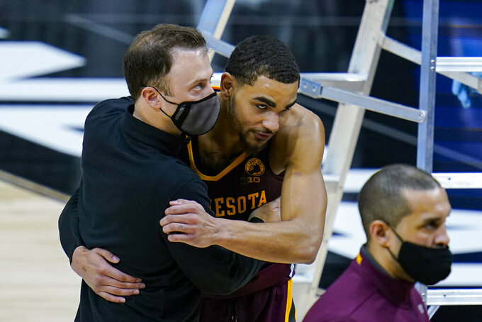 Minnesota head coach Richard Pitino hugs guard Tre' Williams (1) following an NCAA college basketball game against Ohio State at the Big Ten Conference tournament in Indianapolis, Thursday, March 11, 2021. Ohio State defeated Minnesota 79-75. (AP Photo/Michael Conroy)