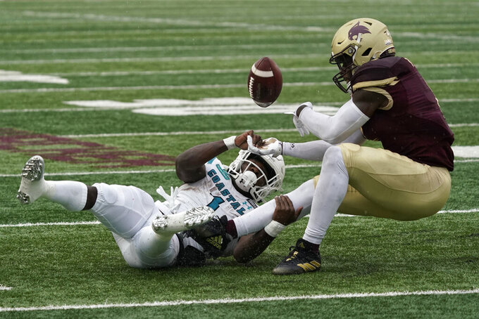 Coastal Carolina's CJ Marable (1) fumbles the ball as he is tackled by Texas State's Hal Vinson, right, during the first half of an NCAA college football game in Austin, Texas, Saturday, Nov. 28, 2020. Marable was ruled down on the play. (AP Photo/Chuck Burton)