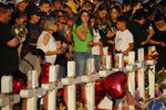 FILE - In this Aug. 6, 2019, file photo, people visit a makeshift memorial at the scene of a mass shooting at a shopping complex in El Paso, Texas. At the growing memorial for the victims of this Saturday massacre, the city's roots in Catholicism and religion in general loom large. (AP Photo/John Locher, File)