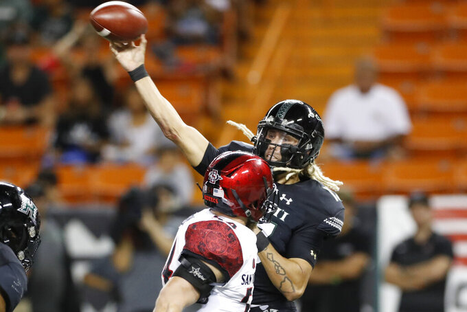 Hawaii quarterback Cole McDonald (13) throws a pass next to San Diego State linebacker Caden McDonald during the first half of an NCAA college football game Saturday, Nov. 23, 2019, in Honolulu. (AP Photo/Marco Garcia)