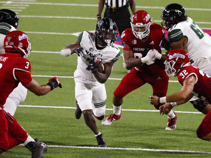 Hawaii running back Calvin Turner runs past Fresno State defensive lineman Colby Warkentin and defensive back Evan Williams, right, during the second half of an NCAA college football game in Fresno, Calif., Saturday, Oct. 24, 2020. (AP Photo/Gary Kazanjian)