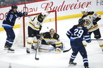 Winnipeg Jets' Mark Scheifele (55) celebrates a goal by Patrik Laine (29) on Boston Bruins goaltender Tuukka Rask (40) as Charlie McAvoy (73) and Patrice Bergeron (37) watch during the first period of an NHL hockey game Friday, Jan. 31, 2020, in Winnipeg, Manitoba. (John Woods/The Canadian Press via AP)