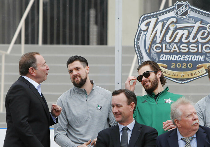 NHL commissioner Gary Bettman, left, chats with Dallas Stars Jamie Benn, center, and Tyler Seguin during a news conference outside the Cotton Bowl in Dallas, Wednesday, March 20, 2019. Sitting in front are Dallas Stars president Brad Alberts, front left, and Nashville Predators chairman Herb Fritch. The group were on hand to announce the NHL Winter Classic hockey game between the Nashville Predators and the Dallas Stars to be played Jan. 1, 2020, at the Cotton Bowl in Dallas. (AP Photo/LM Otero)