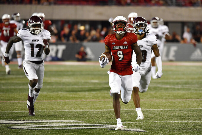 Louisville wide receiver Ahmari Huggins-Bruce (9) runs from the pursuit of Eastern Kentucky defensive back Josh Hayes (12) and cornerback Nic Cheeley (10) during the second half of an NCAA college football game in Louisville, Ky., Saturday, Sept. 11, 2021. (AP Photo/Timothy D. Easley)