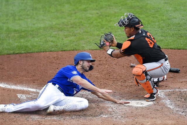 Toronto Blue Jays' Randal Grichuk, left, touches the plate under Baltimore Orioles catcher Pedro Severino to score the winning run on Teoscar Hernández's walkoff two-run single during the ninth inning of a baseball game in Buffalo, N.Y., Sunday, Aug. 30, 2020. (AP Photo/Adrian Kraus)