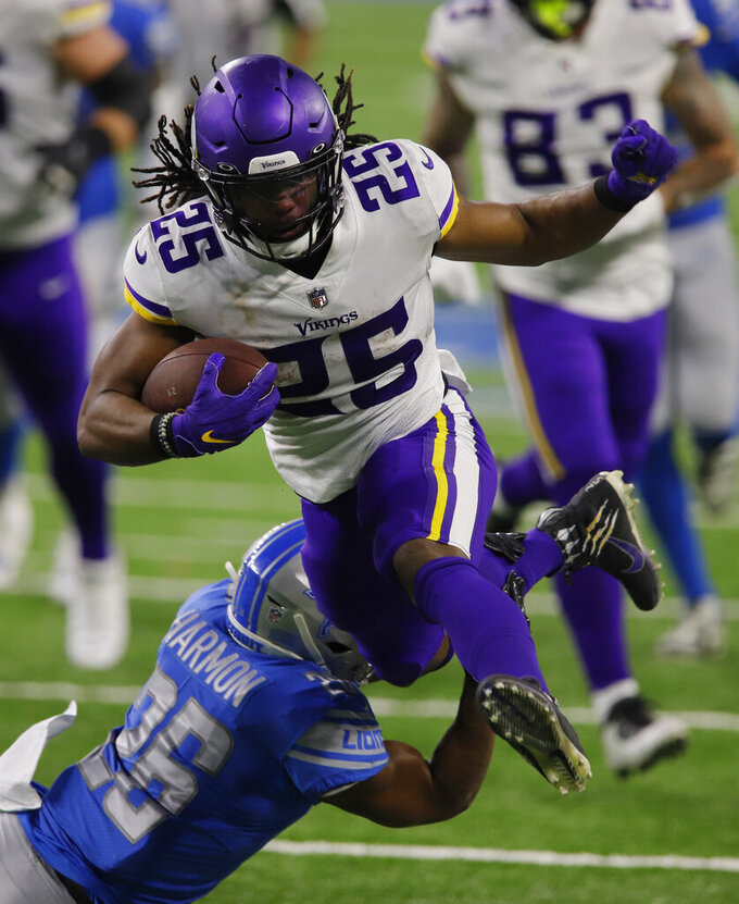 Minnesota Vikings running back Alexander Mattison (25) jumps over Detroit Lions strong safety Duron Harmon (26) during the first half of an NFL football game, Sunday, Jan. 3, 2021, in Detroit. (AP Photo/Al Goldis)
