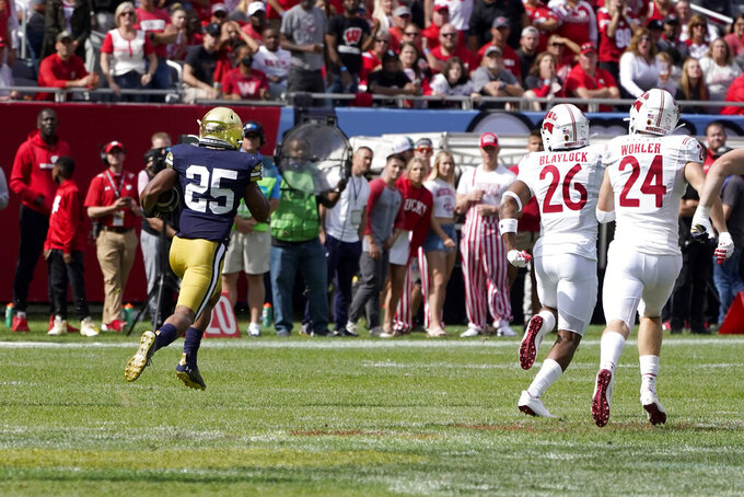 Notre Dame running back Chris Tyree returns a kickoff for a touchdown as Wisconsin safety Travian Blaylock and Hunter Wohler pursue during the second half of an NCAA college football game Saturday, Sept. 25, 2021, in Chicago. Notre Dame won 41-13. (AP Photo/Charles Rex Arbogast)