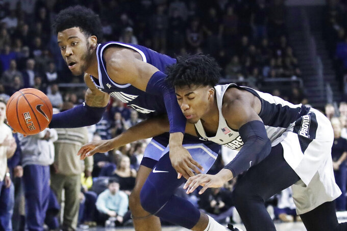 Villanova forward Saddiq Bey, left, controls the ball against Providence guard David Duke, right, in the first half of an NCAA college basketball game, Saturday, Jan. 25, 2020, in Providence, R.I. (AP Photo/Elise Amendola)