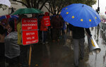 Anti-Brexiteer Steve Bray carries his megaphone past pro Brexit supporters as they shelter from the heavy rain outside the Houses of Parliament in London, Thursday, Oct. 17, 2019. (AP Photo/Alastair Grant)
